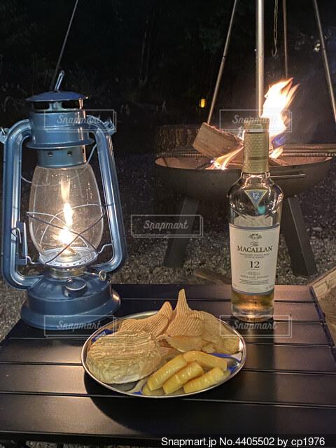 焚火とオイルランタンとウイスキーの写真・画像素材[4405502]