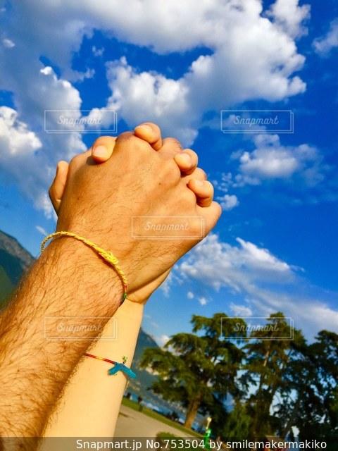 青空の下で手をつなぐカップルの写真・画像素材[753504]