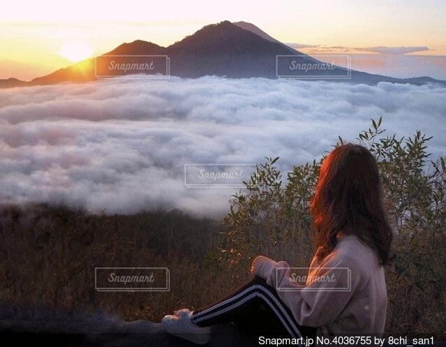 夕日の前に立っている人の写真・画像素材[4036755]