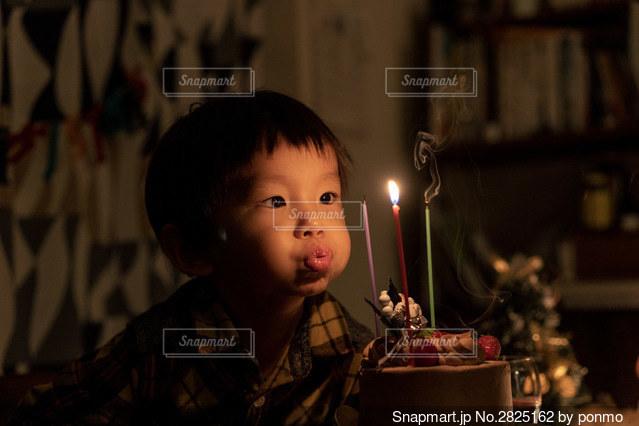 テーブルに座っている若い男の子の写真・画像素材[2825162]