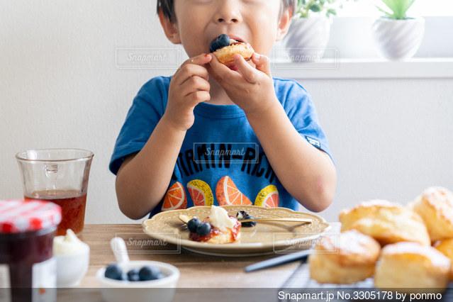 食べ物を食べるテーブルに座っている小さな男の子の写真・画像素材[3305178]