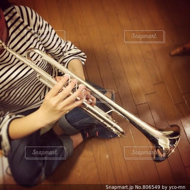 ギターの横の床に座っている人の写真・画像素材[806549]