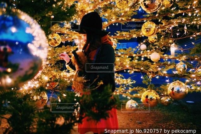クリスマス ツリーの横に立っている人の写真・画像素材[920757]
