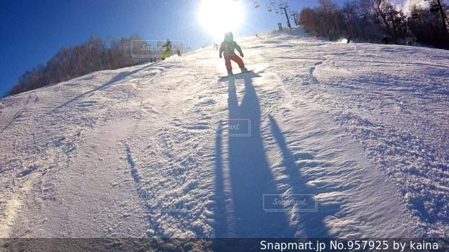 雪に覆われた斜面をスキーに乗る男の写真・画像素材[957925]