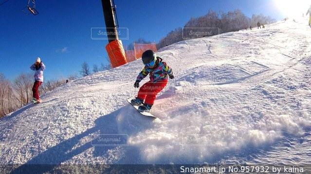 雪をスノーボードに乗る男覆われた斜面の写真・画像素材[957932]
