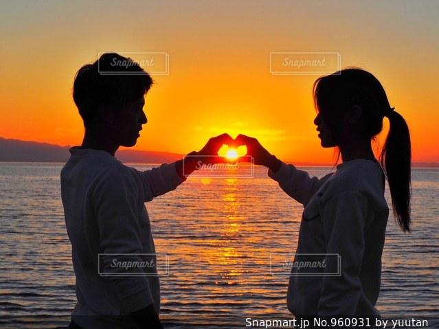 水の体の上に日没の前に立っての写真・画像素材[960931]