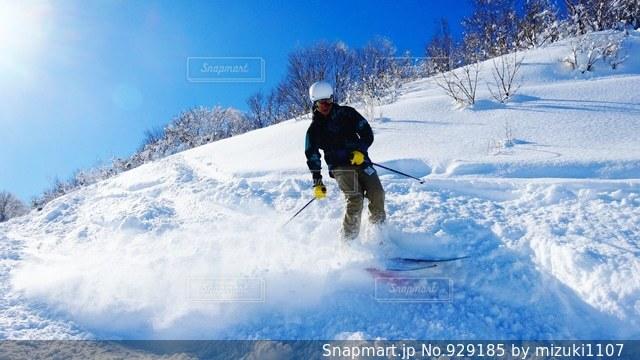 雪に覆われた斜面をスキーに乗る男の写真・画像素材[929185]