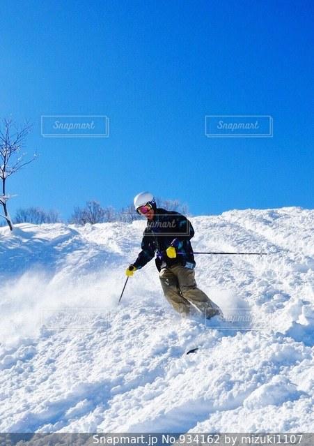 雪に覆われた斜面をスキーに乗る男 - No.934162