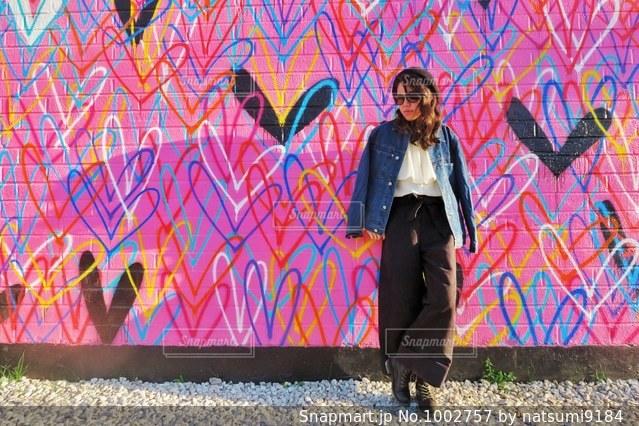 カラフルな壁の前に立っている人の写真・画像素材[1002757]