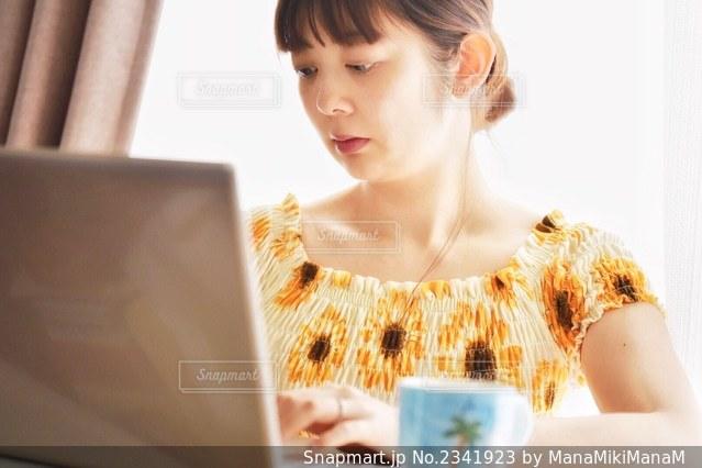 テーブルの上に座っている若い女の子の写真・画像素材[2341923]