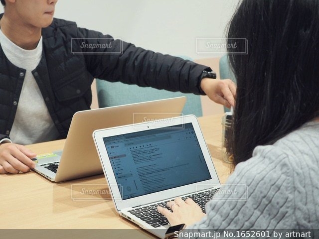 ラップトップ コンピューターを使用してテーブルに座っている女性の写真・画像素材[1652601]
