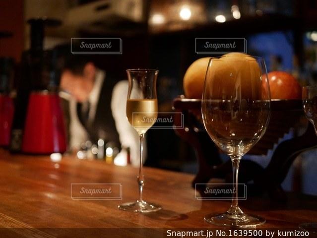 木製テーブルの上に座っているグラスワインの写真・画像素材[1639500]