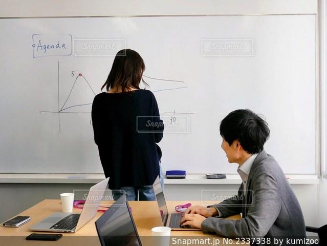 コンピュータの前の机に座っている人の写真・画像素材[2337338]