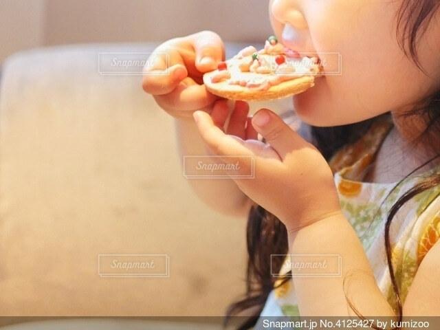 ミニピザをほおばる女の子の写真・画像素材[4125427]