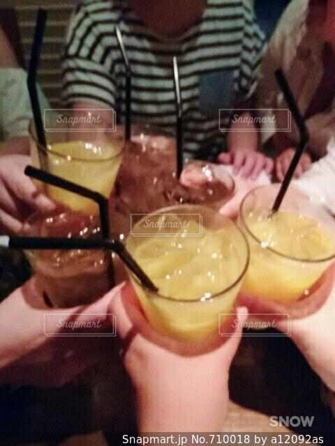 食べ物や飲み物とテーブルに座っている人々 のグループの写真・画像素材[710018]