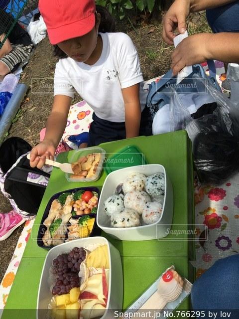 食物と一緒にテーブルに座っている人々 のグループの写真・画像素材[766295]