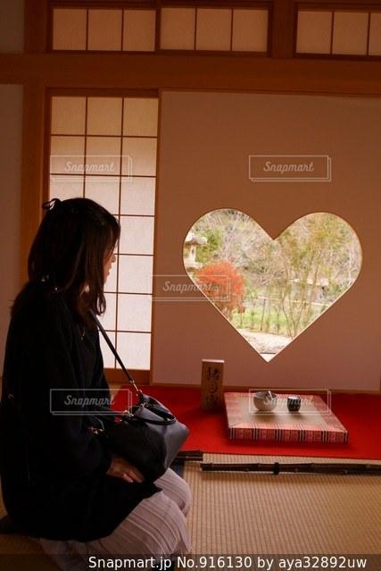 窓の前で机に座っている女性の写真・画像素材[916130]