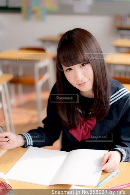 教室の机に座っている女子高生の写真・画像素材[858027]