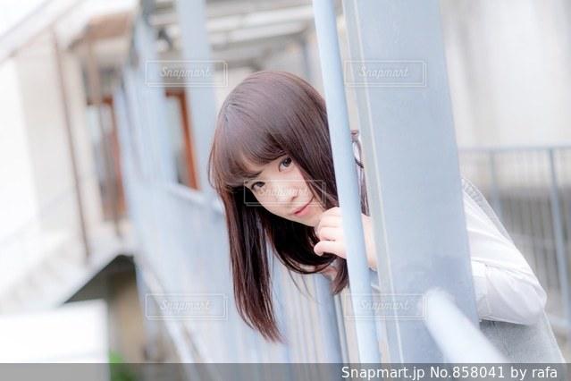 渡り廊下から身を乗り出す女子高生の写真・画像素材[858041]