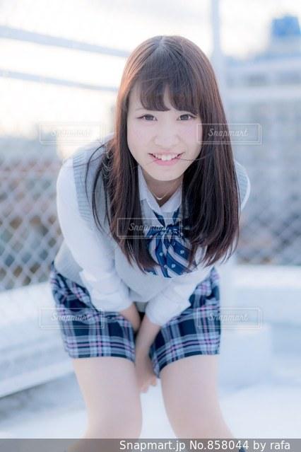 屋上のフェンスの前に立っている女子高生の写真・画像素材[858044]