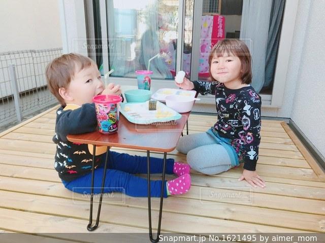テーブルに座っている小さな子供の写真・画像素材[1621495]