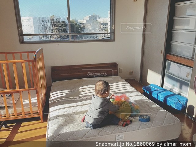 ベッドの上に座っている小さな子供の写真・画像素材[1860069]