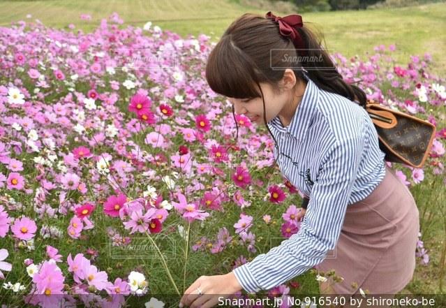 花の前に立っている女性の写真・画像素材[916540]