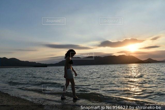 水の体の近くのビーチに立っている人の写真・画像素材[956627]