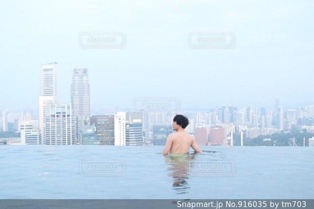 バック グラウンドで市と水体に坐っていた男 - No.916035