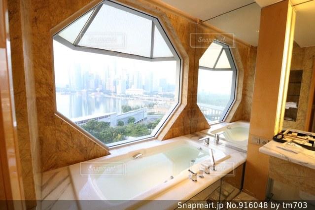 ウィンドウの横に座っている白い浴槽付きのバスルームの写真・画像素材[916048]