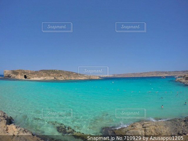水の体の横にある砂浜のビーチの写真・画像素材[710929]