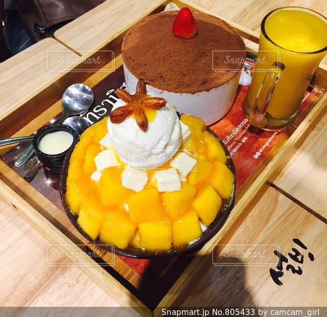 マンゴーたっぷりふわふわかき氷とマンゴジュースの写真・画像素材[805433]