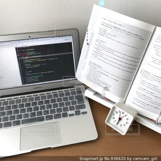 プログラミング学習中のパソコンと参考書の写真・画像素材[938420]