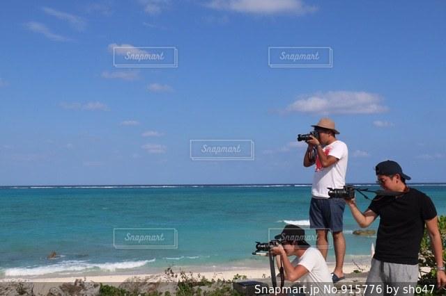 海の横にある砂浜のビーチの上に立っている人 - No.915776