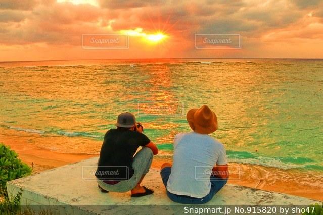 水の体の近くのビーチに座っている男 - No.915820