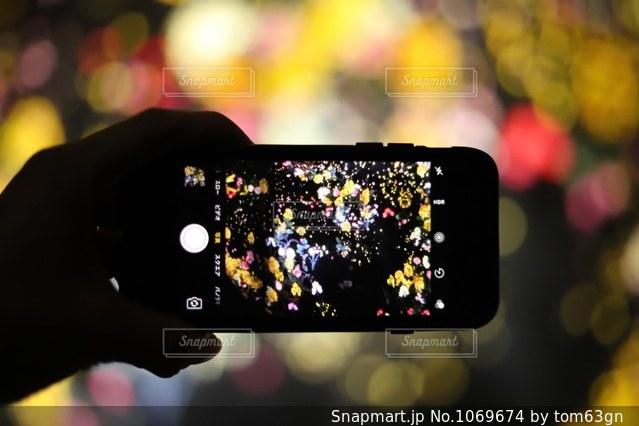 近くに携帯電話を保持している人のの写真・画像素材[1069674]