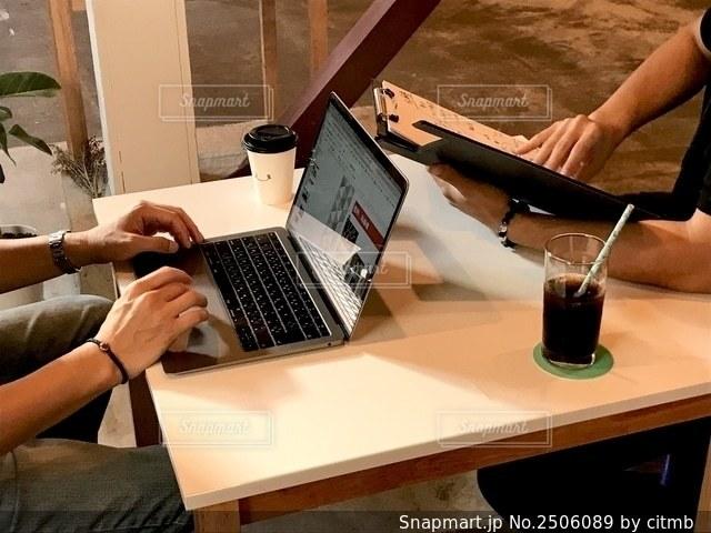 ラップトップコンピュータを使ってテーブルに座っている人の写真・画像素材[2506089]