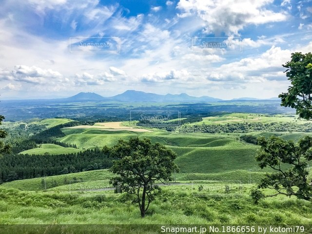 背景の山に大規模なグリーン フィールドの写真・画像素材[1866656]
