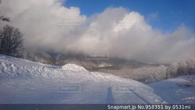 雪に覆われた斜面をスキーに乗る男 - No.958351