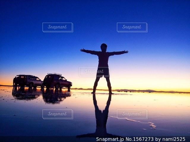 水の体の横に立っている人の写真・画像素材[1567273]