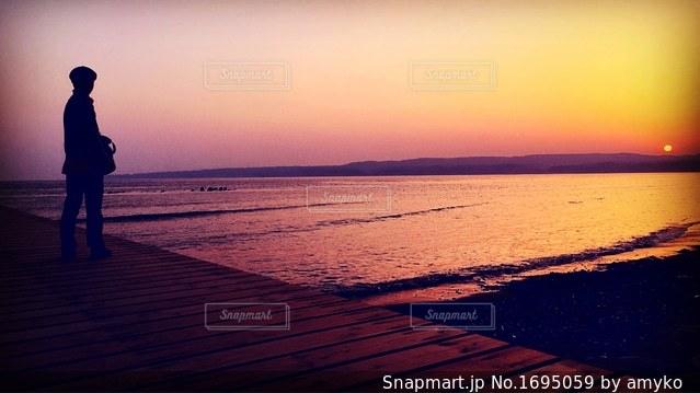 バック グラウンドで夕焼けのビーチに立っている人の写真・画像素材[1695059]