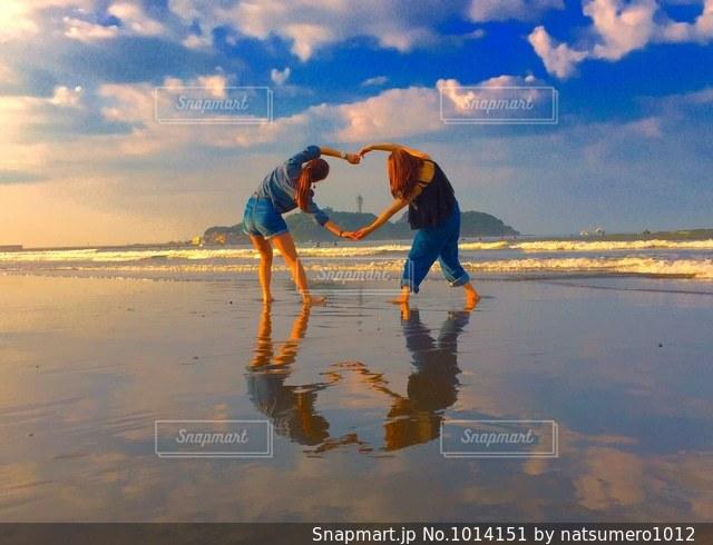水の体の横に立っている人の写真・画像素材[1014151]