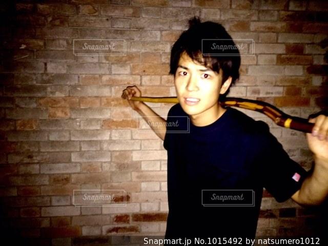 レンガ壁の前に立っている少年の写真・画像素材[1015492]
