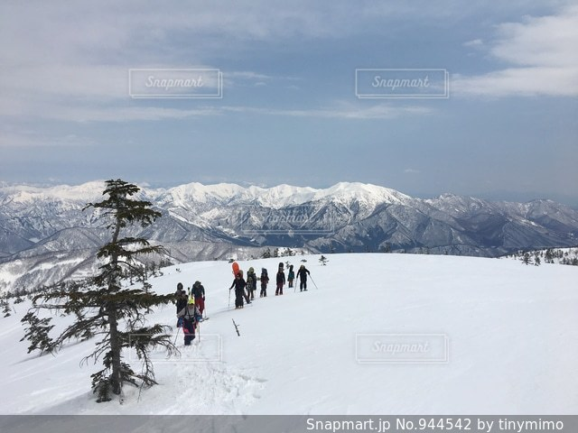 雪の山でスキーに乗っている人のグループの写真・画像素材[944542]