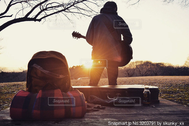 夕陽とギターの写真・画像素材[3203791]