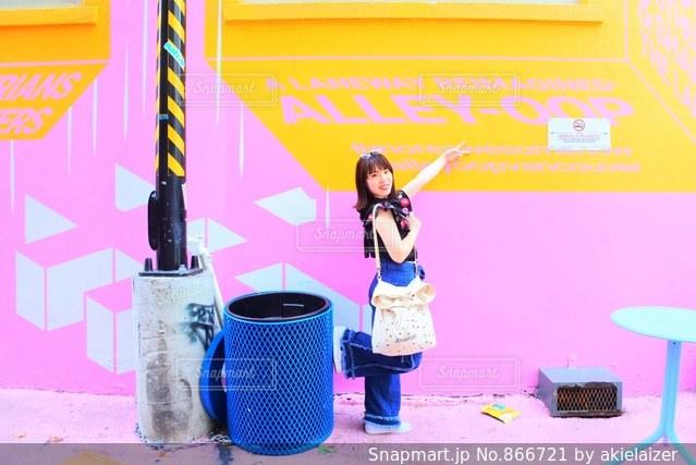 ピンクのオシャレな壁の前でポーズする女の子の写真・画像素材[866721]
