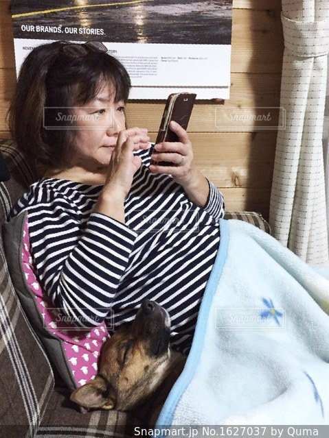 携帯電話で話している椅子に座っている女性の写真・画像素材[1627037]
