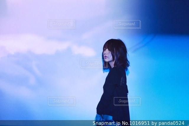 青い空の前に立っている人の写真・画像素材[1016951]