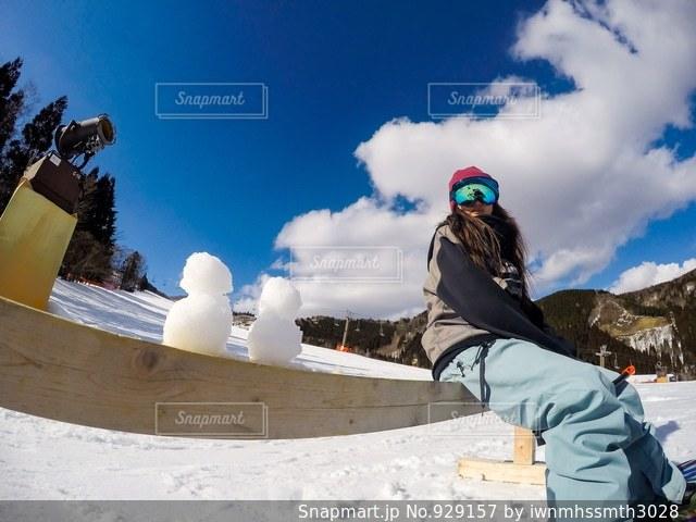 雪をスノーボードに乗る女覆われた斜面の写真・画像素材[929157]