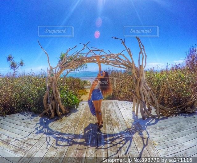 ヤシの木の横に立っている人の写真・画像素材[898770]